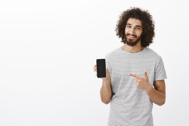 De beste keuze voor moderne mensen. blij knap mannelijk model met baard in gestreept t-shirt, smartphone tonen en apparaat met wijsvinger wijzend, breed glimlachend