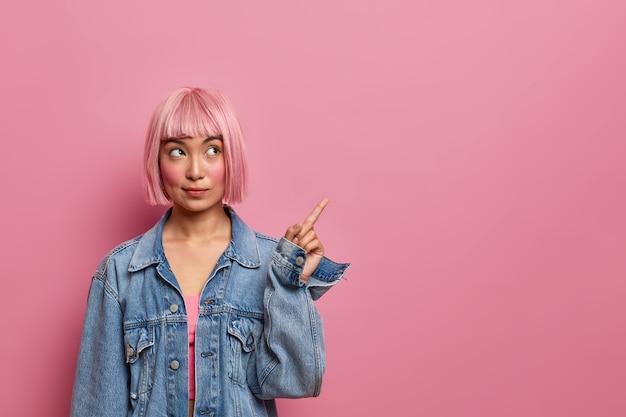 De beste kopieerruimte voor jou. ernstig uitziende aziatische vrouw met trendy kapsel, wijst weg, overtuigt klant om haar product te kopen, draagt spijkerkleding, heeft een doordachte blik. reclame concept