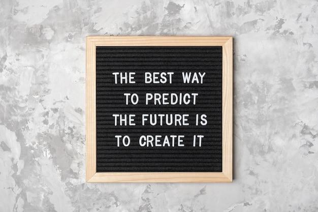 De beste manier om de toekomst te voorspellen, is door hem te creëren. motiverende citaat op zwarte letter bord op grijze achtergrond. concept inspirerende quote van de dag. wenskaart, briefkaart.