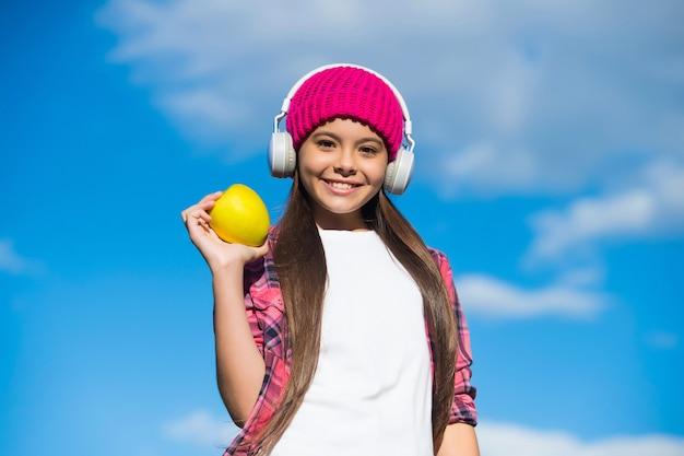 De beste manier om uw vitamines in te nemen. gelukkig kind houdt appel op zonnige blauwe hemel. vitamine tussendoortje. juiste koolhydraten eten. gezond eten. energie dieet. natuurlijke vitamines.