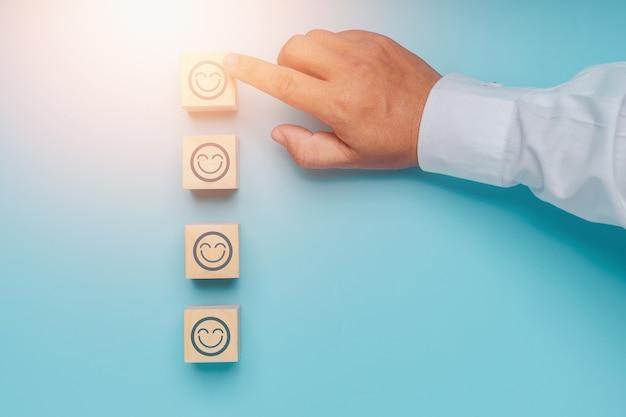 De beste uitstekende beoordeling voor zakelijke services met een blij gezicht en een glimlach naar het concept van de klantervaring van vijf juiste maatstreepjes op houtblok op blauwe achtergrond.