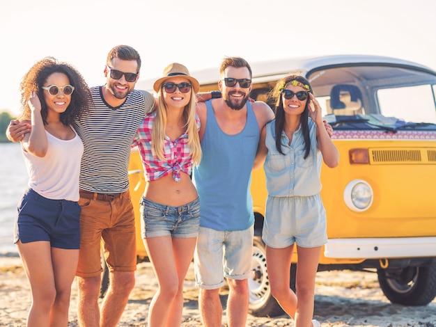 De beste vrienden ooit. groep vrolijke jonge mensen omarmen en kijken naar de camera terwijl ze op het strand staan met retro minibus op de achtergrond