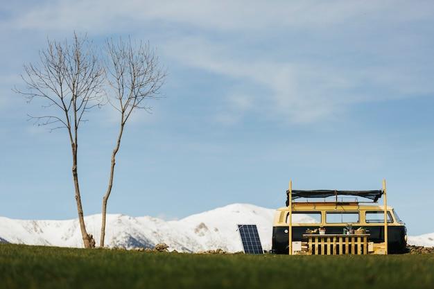 De bestelwagen van de voedselvrachtwagen op een groen gebied met sneeuw bebouwde bergen