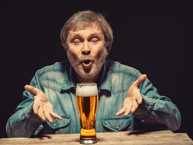 De betoverde man in denim overhemd met glas bier