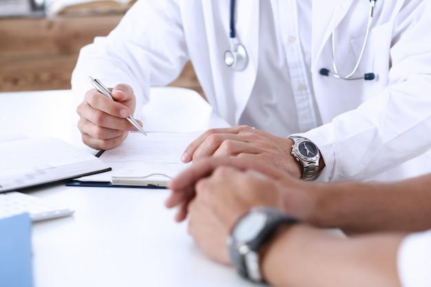 De betrokken knappe arts communiceert met patiënt