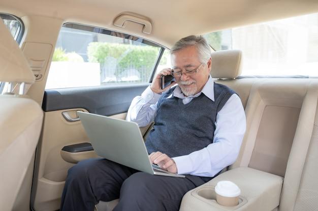 De beurshandelaar die van bedrijfs hogere rijke mensen met laptop computer werken die een slimme telefoon met behulp van
