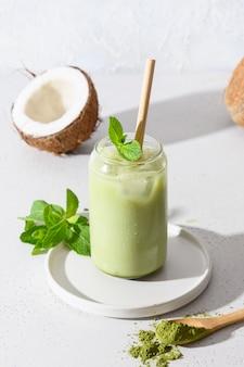 De bevroren latte groene matchathee met kokosmelk versiert munt op witte achtergrond.