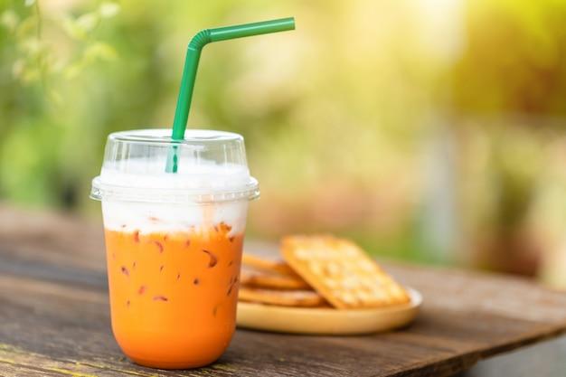 De bevroren thaise thee in duidelijke plastic kop diende op houten lijst in tuincafé.