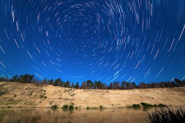 De beweging van sterren rond de poolster op de achtergrond van de rivier