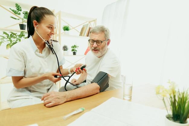 De bezoekende verpleegkundige of gezondheidsbezoeker die voor de senior man zorgt