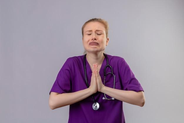 De bezorgde jonge arts die paarse medische jurk en stethoscoop draagt, toont bidgebaar op geïsoleerde witte muur