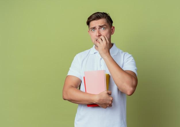 De bezorgde jonge knappe mannelijke boeken van de studentenholding en bijtspijkers die op olijfgroene achtergrond worden geïsoleerd
