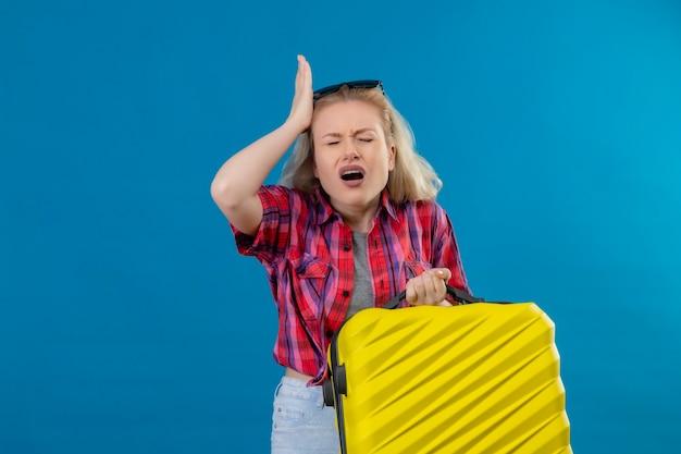 De bezorgde jonge vrouwelijke reiziger die een rood overhemd en een bril op het hoofd draagt en een koffer houdt, legt haar hand op het hoofd op de geïsoleerde blauwe muur