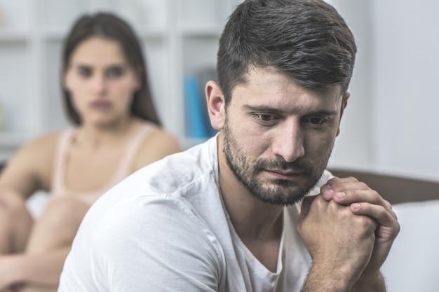 De bezorgde man zit naast de vrouw op het bed