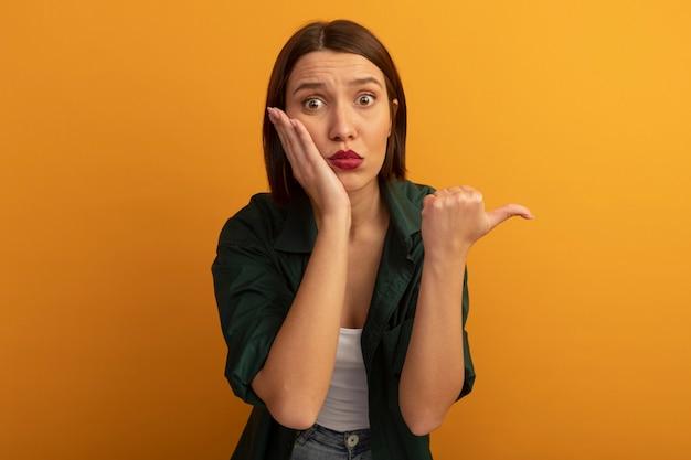 De bezorgde vrij blanke vrouw legt de hand op het gezicht en wijst naar de zijkant op oranje