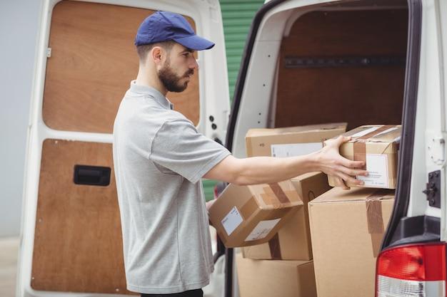 De bezorger die van de levering pakketten houdt om zijn bestelwagen te laden