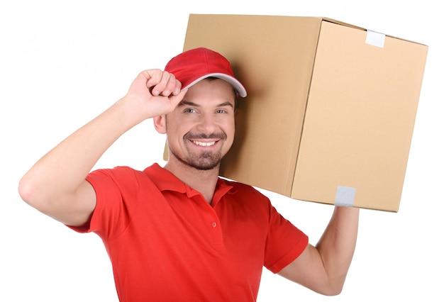 De bezorger houdt een doos op zijn schouder.