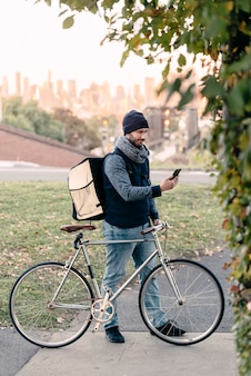 De bezorger van het eten controleert nieuwe bestellingen in zijn smartphone terwijl hij zijn fiets vasthoudt