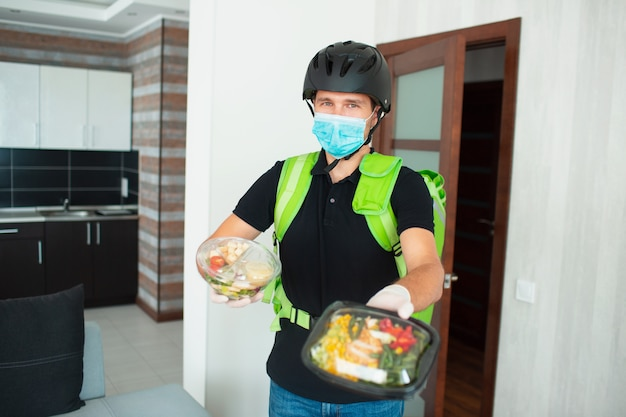 De bezorger van het eten kijkt naar de camera in het huis. hij houdt de bestelling in zijn handen. zijn gezicht is bedekt met een masker.