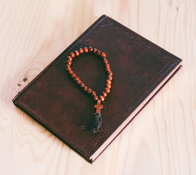 De bijbel en houten rozenkrans op de tafel, bovenaanzicht close-up