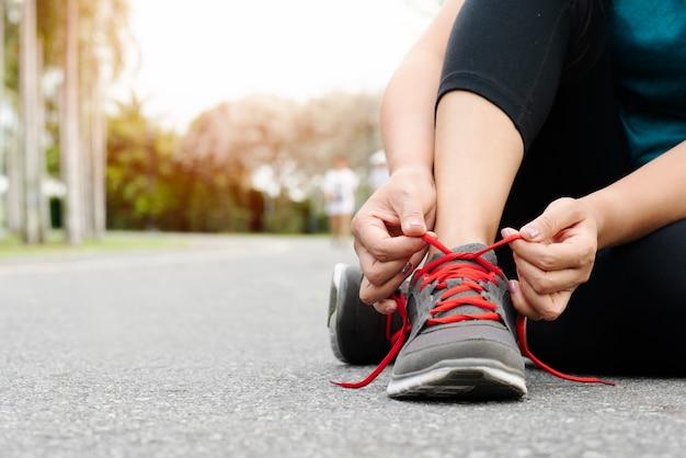 De bindende schoenveter van de sportvrouw alvorens te lopen
