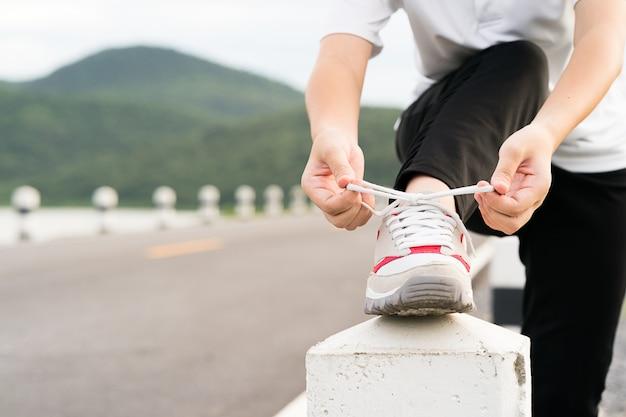 De bindende schoenveter van de vrouw van hem alvorens met het lopen te beginnen