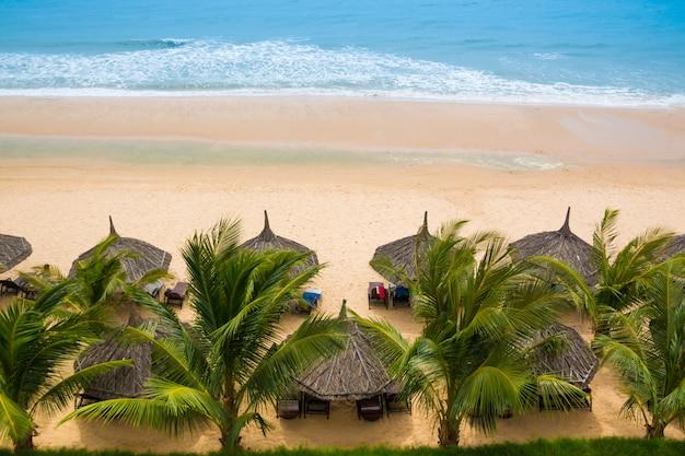 De bladeren van bruine rieten parasols op het strand