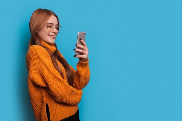 De blanke gembervrouw met sproeten maakt reclame voor iets op een blauwe muur met vrije ruimte terwijl ze aan het telefoneren is en een bril draagt