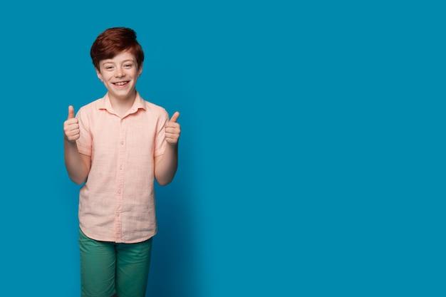 De blanke jongen met rood haar gebaart hetzelfde teken op een blauwe studiomuur met vrije ruimte die iets adverteert
