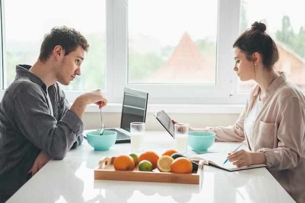 De blanke man eet granen en met behulp van een laptop kijkt naar zijn vrouw die melk drinkt en iets schrijft