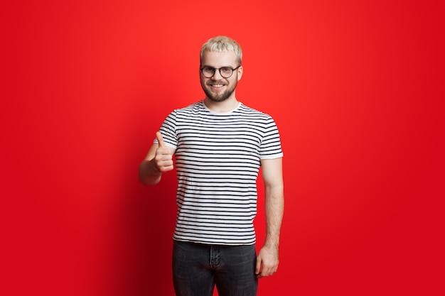 De blanke man met blond haar en een bril gebaart het soortgelijk teken dat bij camera op een rode studiomuur glimlacht