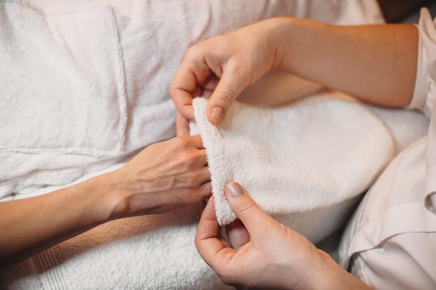 De blanke masseur brengt een speciale handschoen aan op de hand van de cliënt voordat hij aan de volgende spa-procedure begint