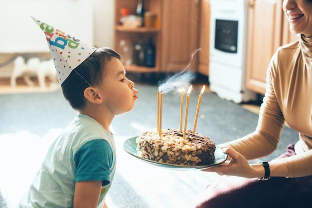 De blanke moeder houdt de taart vast terwijl de zoon op zijn verjaardag de kaarsjes blaast die een feestmuts dragen