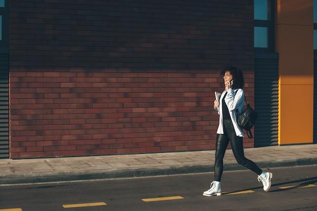 De blanke onderneemster loopt op een straat en spreekt over telefoon die laptop houdt