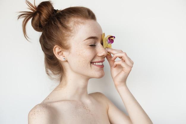 De blanke vrouw bedekt haar oog met een bloem die met blote schouders op een witte studiomuur stelt