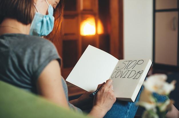 De blanke vrouw die een speciaal masker draagt, schrijft iets in een boek terwijl ze op de bank zit