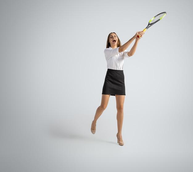 De blanke vrouw in bureaukleren speelt tennis dat op grijze muur wordt geïsoleerd
