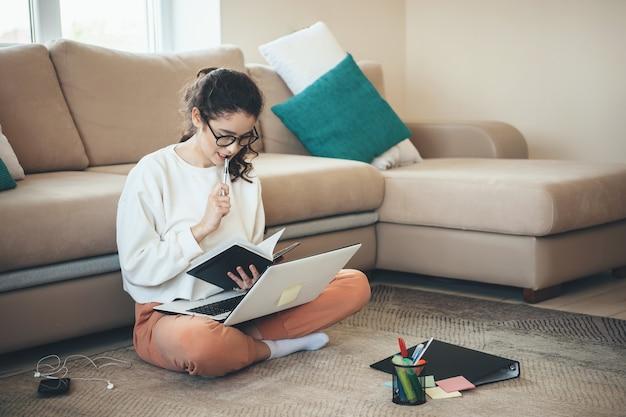 De blanke vrouw is geconcentreerd op het maken van huiswerk terwijl ze op de grond zit met een laptop en een boek
