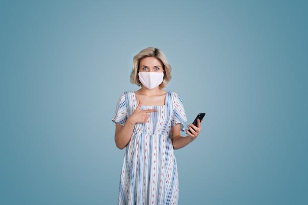 De blanke vrouw met blond haar en masker die een jurk draagt, wijst verbaasd naar haar telefoon op een blauwe studiomuur