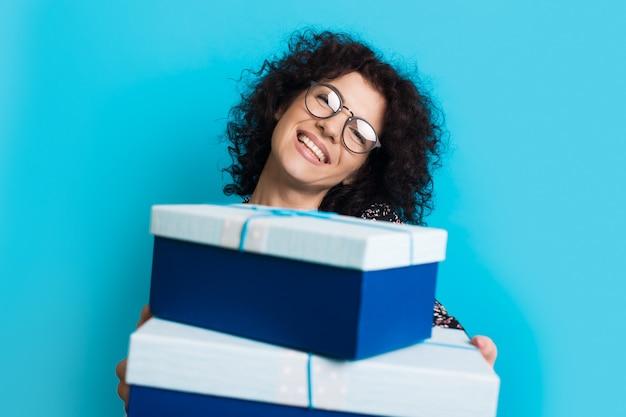 De blanke vrouw met krullend haar en een bril geeft een cadeautje naar de camera die lacht op een blauwe studiomuur