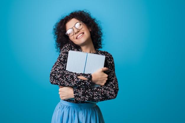 De blanke vrouw met krullend haar omhelst een cadeau dat glimlacht vooraan op een blauwe muur die een jurk draagt