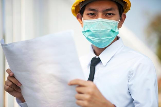 De blauwdruk van de ingenieursholding draagt het medische werk van het gezichtsmasker bij bouwwerf