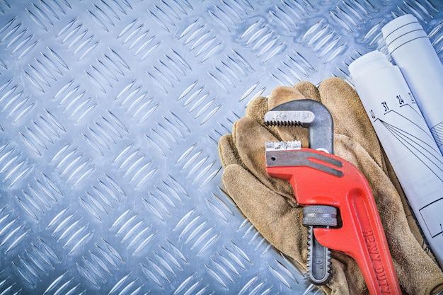 De blauwdrukken leer beschermende handschoenen van de aapmoersleutel op gegroefd metaal achtergrondbouwconcept