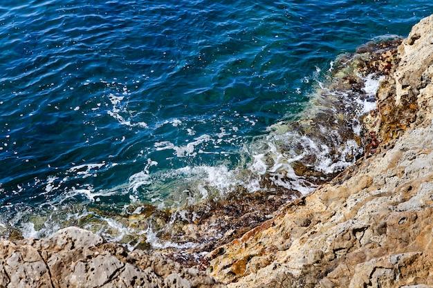 De blauwe adriatische zee, de golf is gebroken tegen de rotsen