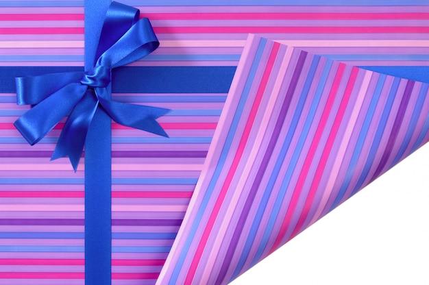 De blauwe boog van het giftlint op het inpakpapier van de suikergoedstreep, gevouwen hoek open tonend witte exemplaarruimte