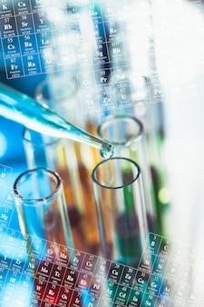 De blauwe druppel van de pipet over laboratoriumbuizen en de achtergrond van het periodiek systeem