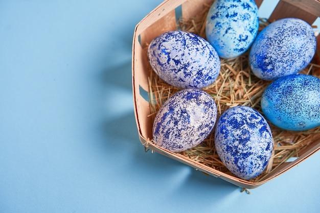 De blauwe eieren van pasen in mand op blauwe achtergrond