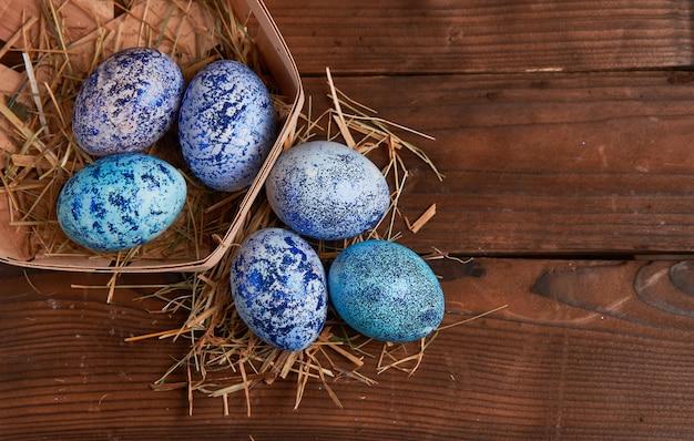 De blauwe eieren van pasen in mand op houten achtergrond
