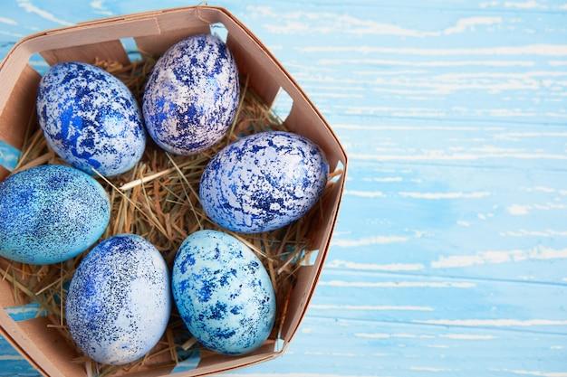 De blauwe eieren van pasen in mand op houten lijst