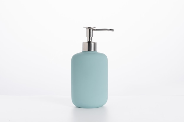 De blauwe fles van de glaszeep die op een witte muur wordt geïsoleerd